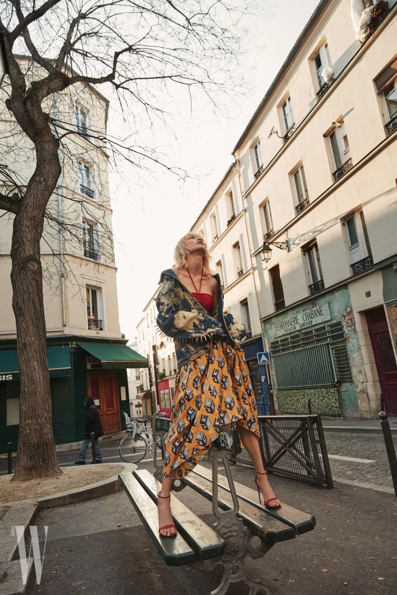 스터드 장식의 워싱 데님 재킷과 훌터넥 스타일의 셔링 브라톱, 패턴 스커트, 앵클 스트랩 힐은 모두 Gucci 제품.
