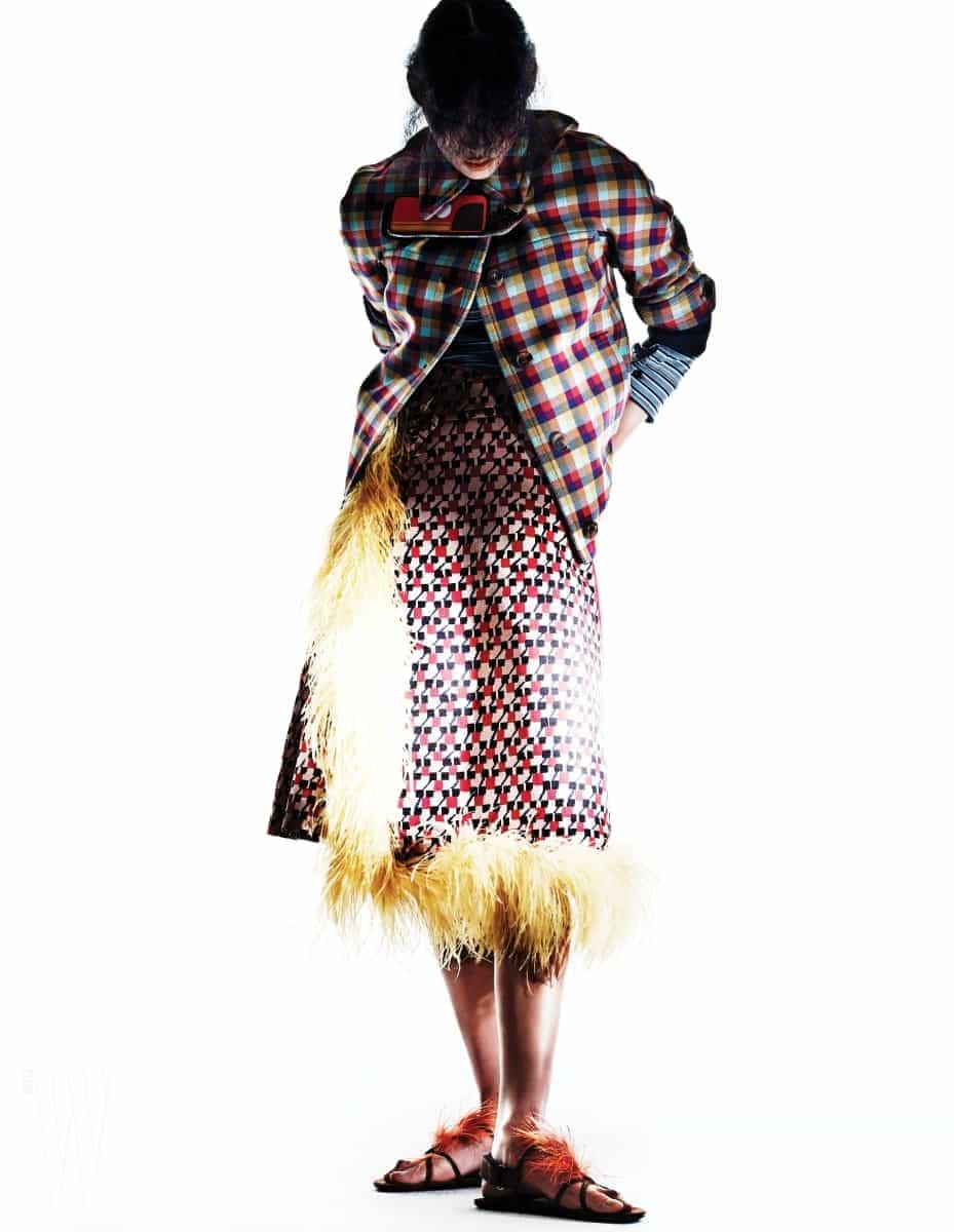 체크무늬 재킷, 안에 입은 줄무늬 톱, 깃털 장식이 달린 그래픽 무늬 스커트, 깃털 장식 플랫 샌들은 모두 프라다 제품. 모두 가격 미정.