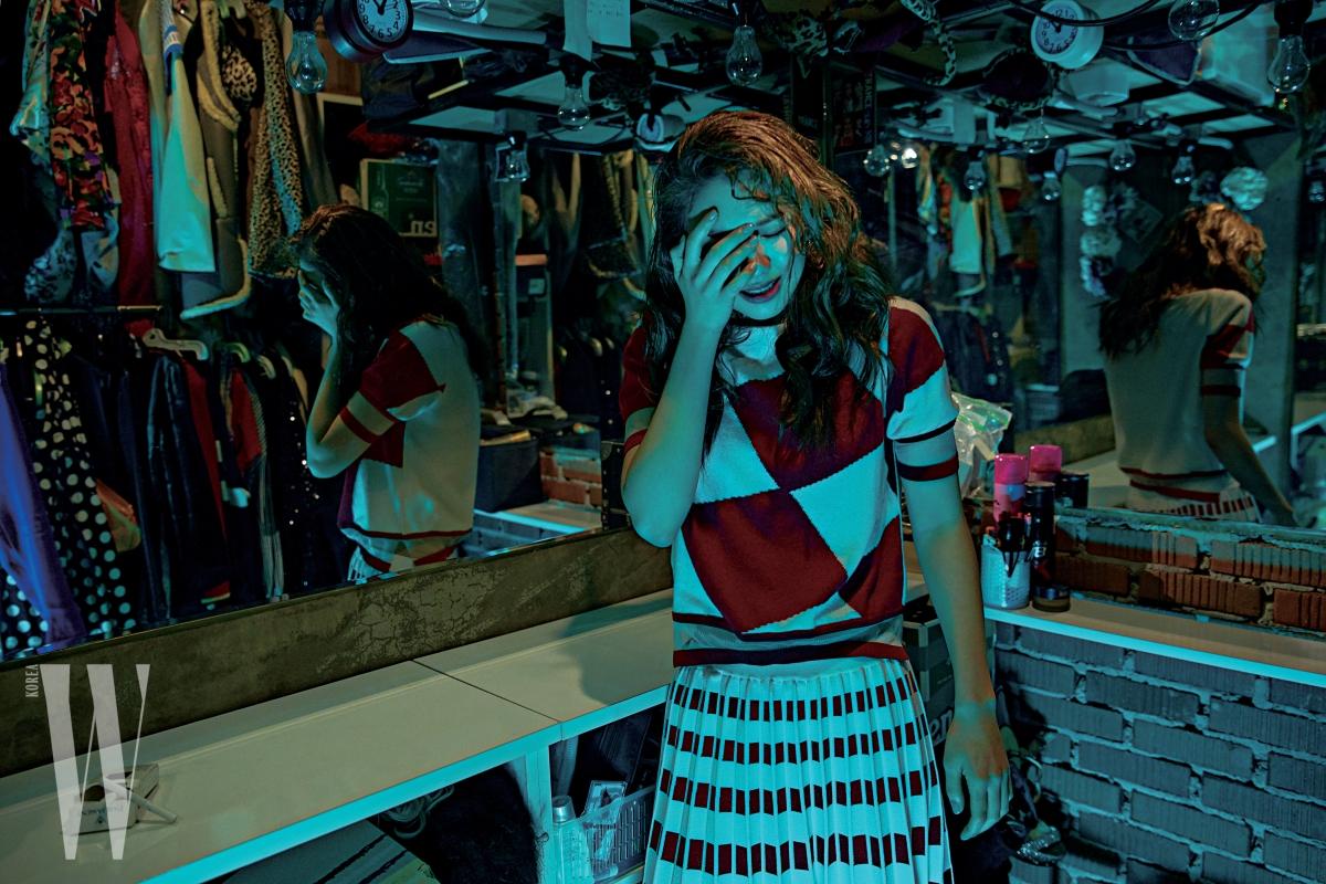 김진경이 입은 체크 패턴 니트 톱과 주름 스커트는 Fendi 제품.