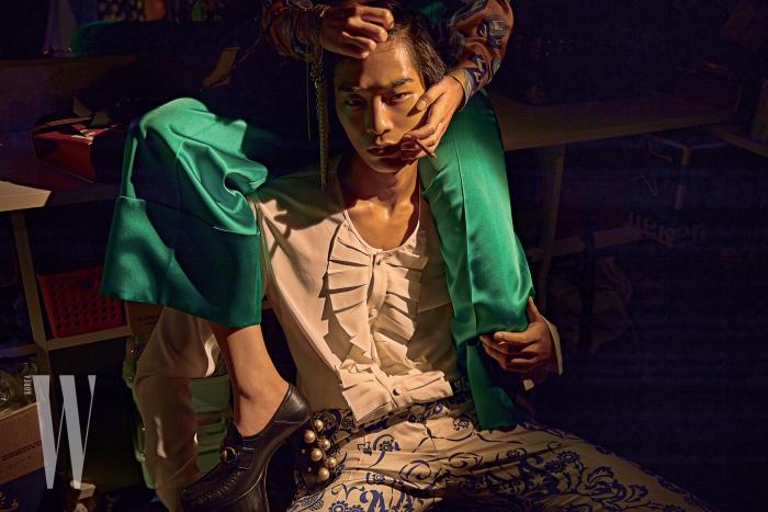 이명관이 입은 여유로운 실루엣의 러플 셔츠와 화려한 패턴이 그려진 팬츠는 Kimseoryong Homme 제품. 정호연이 입은 실크 소재 패턴 셔츠와 녹색 팬츠, 진주 장식 슈즈는 모두 Gucci, 손목에 감은 목걸이는 Chanel 제품.