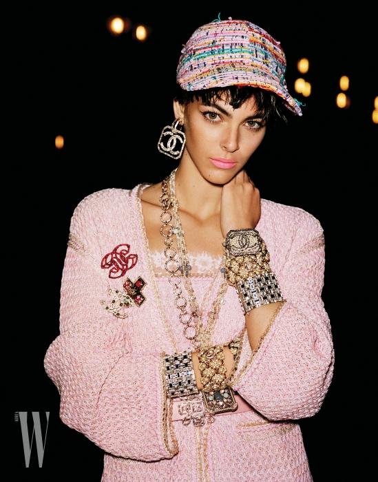 안에 입은 레이스 톱, 트위드 드레스, 겉에 걸친 카디건, 싱글 로고 귀고리, 목걸이, 브로치, 팔찌와 벨트는 모두 Chanel 제품.
