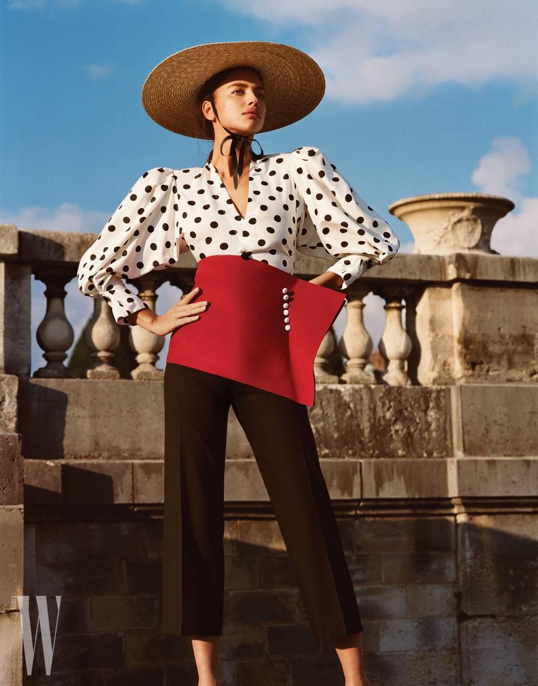도트 블라우스, 팬츠, 모자와 입체적인 벨트는 모두 Jacquemus 제품.