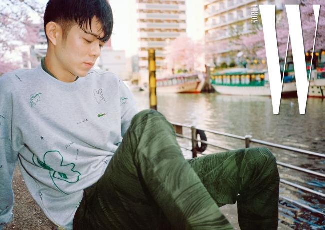 그레이 색상의 트로피컬 프린트 스웨트셔츠와 안에 겹쳐 입은 카키색 피케 폴로 셔츠, 나무 질감을 표현한 프린트가 독특한 치노 팬츠는 Lacoste Live 제품.