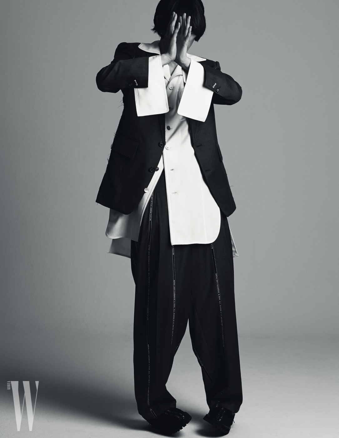 회색 재킷과 라펠이 넓은 넉넉한 셔츠, 줄무늬 패턴 회색 팬츠, 슈즈는 모두 Munn 제품.