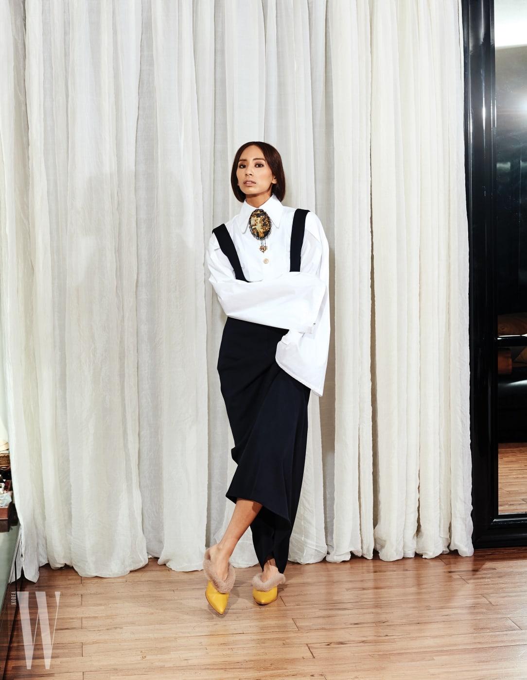 안나가 입은 긴소매 셔츠와 오버올 드레스, 고풍스러운 브로치, 앞코가 뾰족한 퍼 장식 슈즈는 모두 Miss Gee Collection 제품.