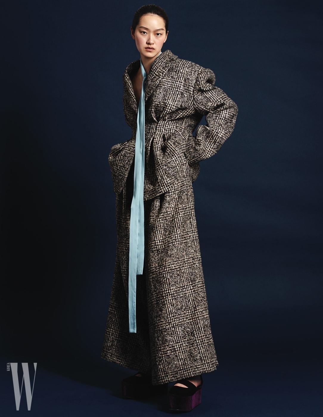 풍성한 어깨, 잘록한 허리가 특징인 클래식한 재킷, 와이드 팬츠, 하늘색 실크 타이, 밸벳 소재의 웨지 샌들은 모두 Jinteok 제품.