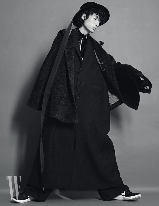 검은색 맥시 코트와 후드가 달린 케이프, 안에 입은 벨벳 소재의 트레이닝 점퍼, 와이드 팬츠, 긴 끈이 달린 페도라는 모두 Munsoo Kwon 제품. 슈즈는 Nike 제품.