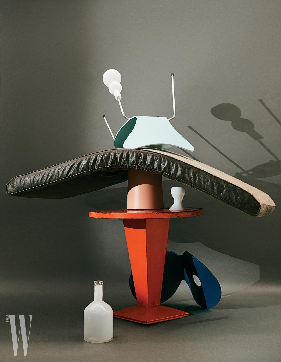 위부터ㅣ동그란 곡선 실루엣의 유리 화병은 Zara Home, 단순하고 아름다운 형태로 시대를 초월한 의자로 꼽히는 Series 7 Chair는 Fritz Hansen, 매트리스 아래 놓인 소일 핑크 컬러 튜블러 휴지통은 Ideaco by WxDxH, 오른쪽의 화병은 Orer 소장품, 오렌지 라운드 철제 테이블은 Tolix, 바닥에 놓인 파란 Series 7 Chair는 의자는 Fritz Hansen, 하얀색 유리 화병은 Casamia 제품.