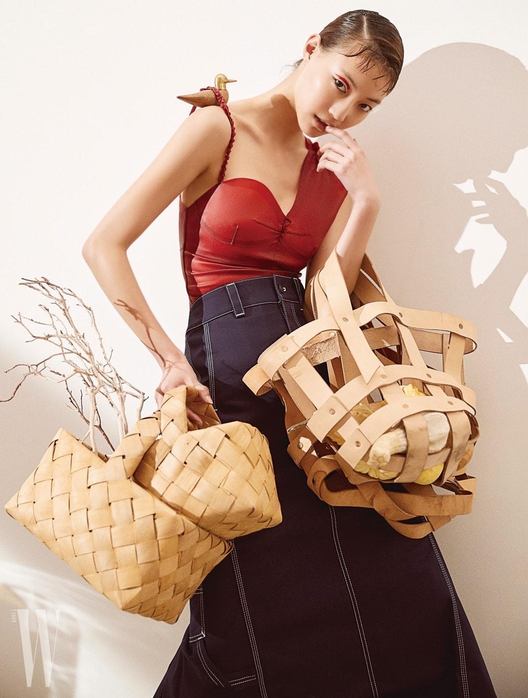 빨간색 보디슈트는 Louis Vuitton, 롱 데님 스커트는 Vetements X Carhartt by 10 Corso Como 제품. 나무껍질로 짠 바구니와 가방으로 연출한 베지터블 가죽으로 만든 화분 바구니, 나무, 과일 오브제는 모두 Verythings 제품.