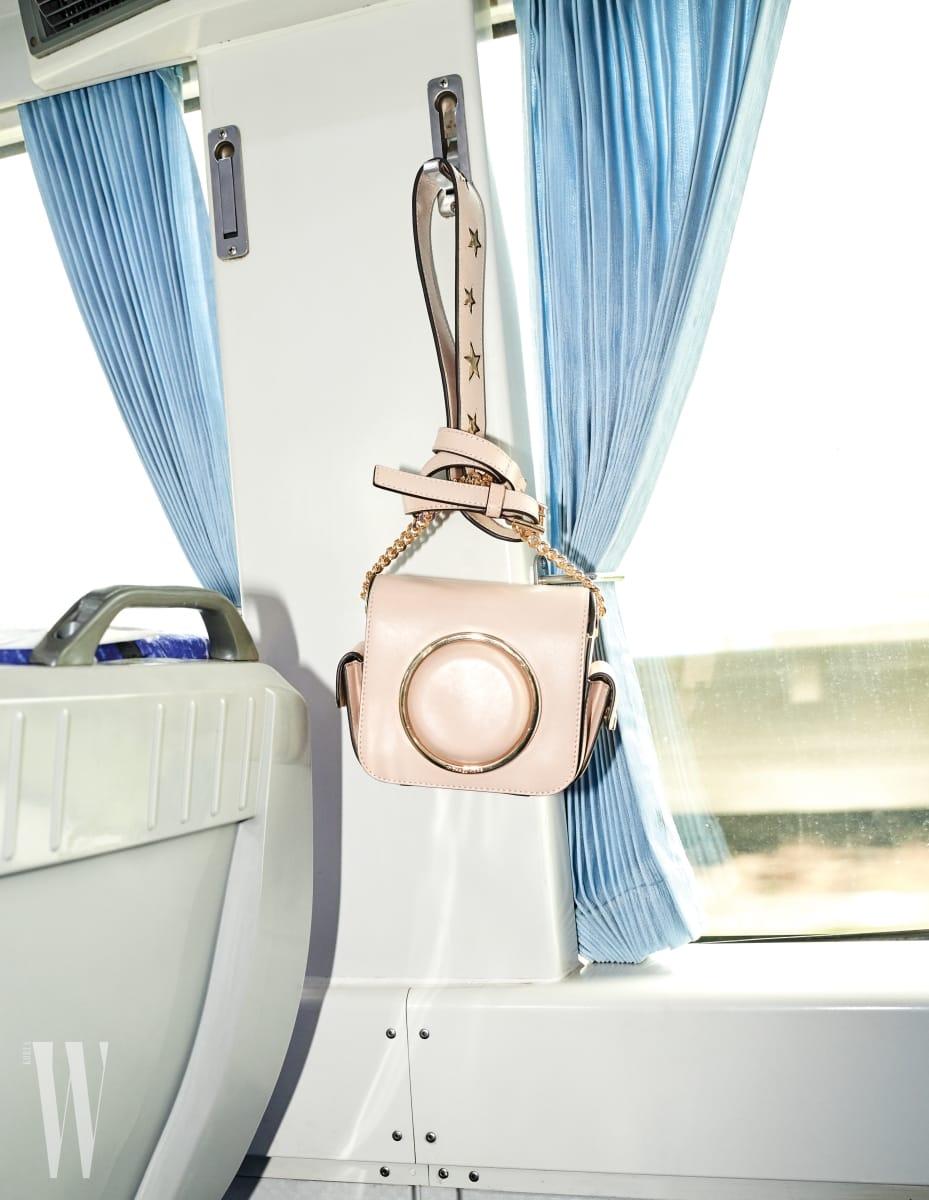 6. 옷걸이에 걸어놓은 폴라로이드 카메라 백은 마이클 코어스 제품. 71만원.