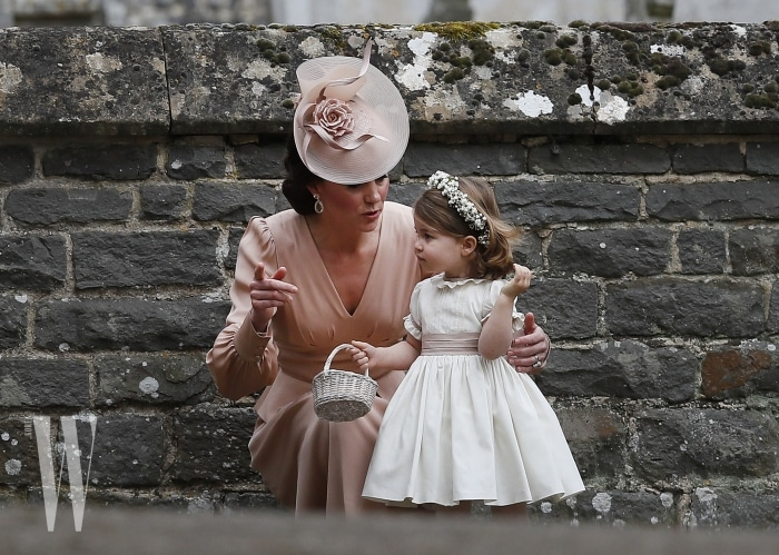 ENGLEFIELD, ENGLAND - MAY 20:  Catherine, Duchess of Cambridge speaks to Princess Charlotte after the wedding of Pippa Middleton and James Matthews at St Mark's Church on May 20, 2017 in in Englefield, England. Middleton, the sister of Catherine, Duchess of Cambridge married hedge fund manager James Matthews in a ceremony Saturday where her niece and nephew Prince George and Princess Charlotte was in the wedding party, along with sister Kate and princes Harry and William. (Photo by Kirsty Wigglesworth - Pool/Getty Images)