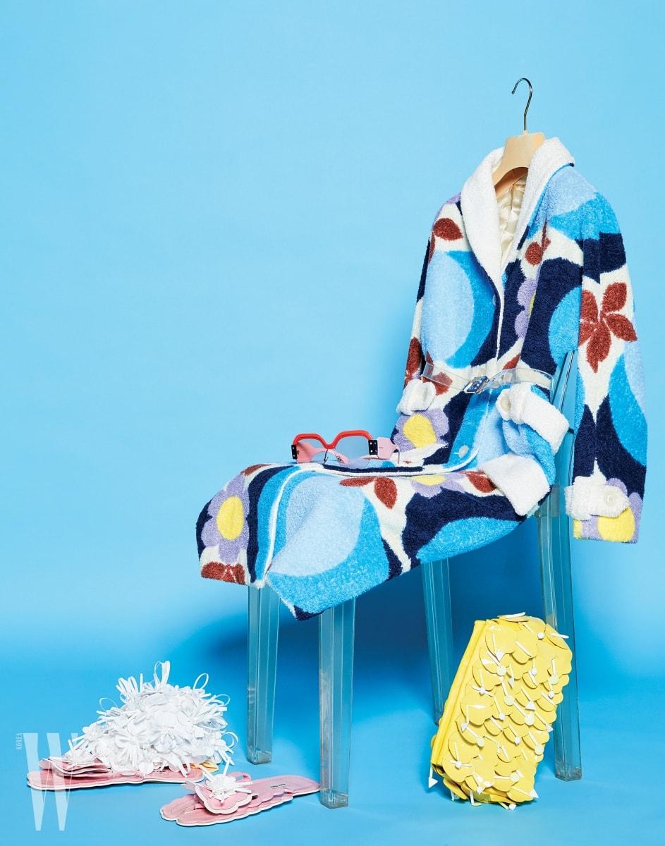 꽃무늬가 담긴 푸른색 로브는 미우미우 제품. 가격 미정. 풍성한 꽃 장식이 돋보이는 수영모는 미우미우 제품. 90만원대. 큼직한 핑크색 렌즈와 프레임이돋보이는 선글라스는 미우미우 제퓸. 가격 미정. 발등의 꽃 장식 슬리퍼는 미우미우 제품. 1백20만원대. 노랑 꽃 장식을 배열한 클러치는 미우미우 제품. 3백40만원대.
