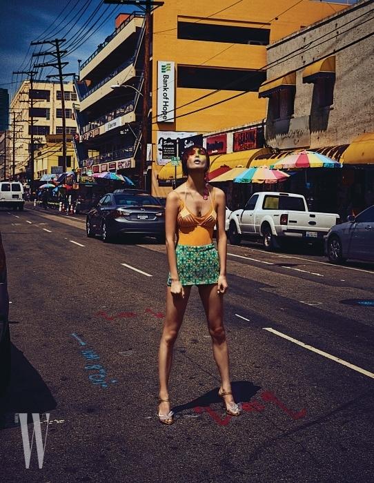 노란색 원피스 수영복, 그 위에 겹쳐 입은 비키니 톱은 모두 H&M, 프린트 스커트는 Prada, 투명 꽃 장식 슈즈는 Miu Miu 제품.