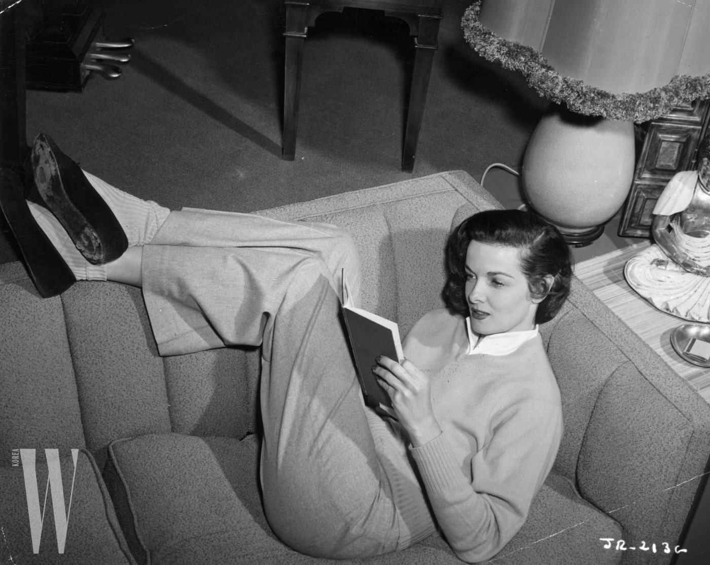 23rd August 1951:  American actress Jane Russell reading at home. width=