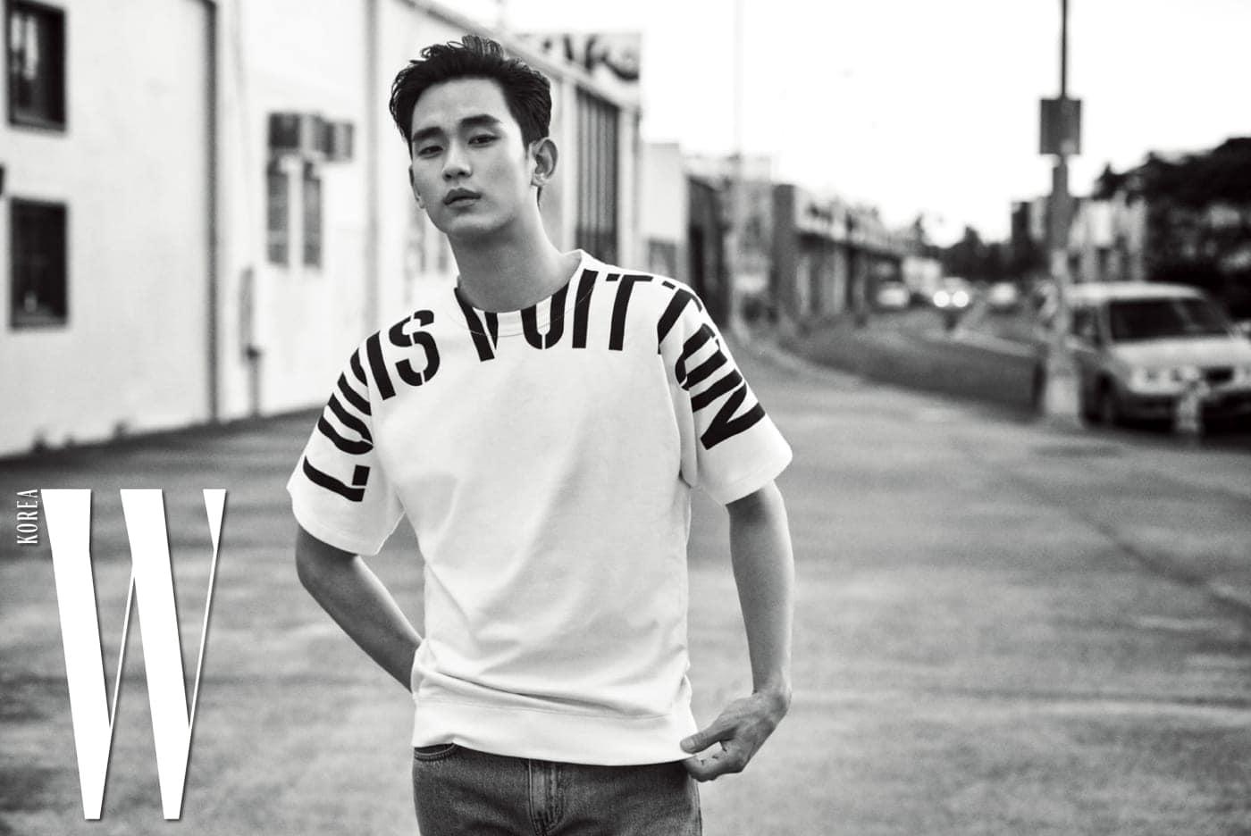어깨 라인을 두르고 있는 그래픽 로고가 인상적인 티셔츠, 데님 팬츠는 Louis Vuitton 제품.
