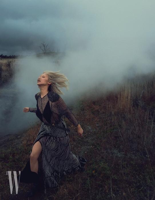 시스루 톱이 어우러진 관능적인 슬릿 장식 롱 드레스와 슈즈는 Louis Vuitton 제품.