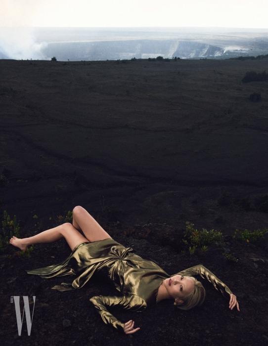 유연한 실루엣이 관능적인 금빛 라메 드레스와 태슬 장식 귀고리는 Saint Laurent 제품.