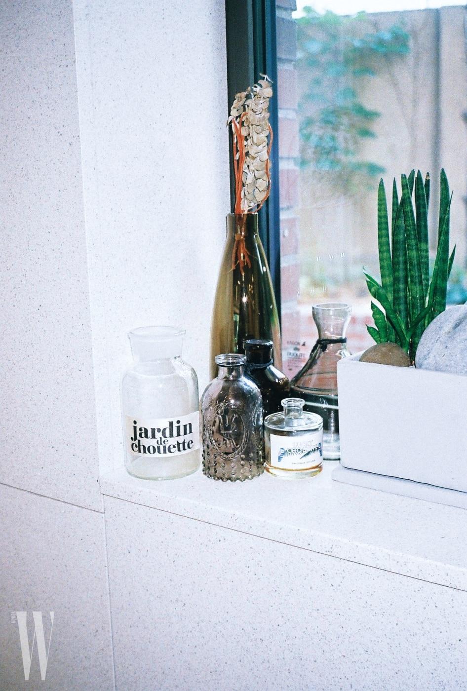럭키 슈에뜨의 전신인 자뎅 드 슈에뜨 로고가 반갑다. 창가에 놓인 유리병과 식물들.