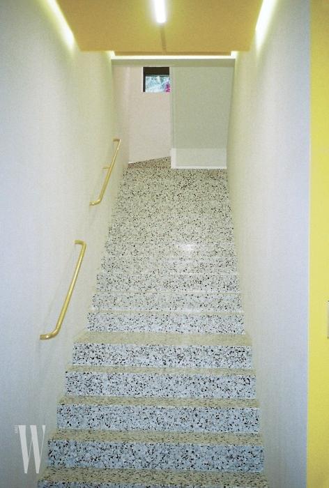 지하로 내려가는 계단은 마치 어느 럭셔리 패션 부티크로 향하는 공간처럼 느껴진다. 벽의 금색 손잡이가 포인트.