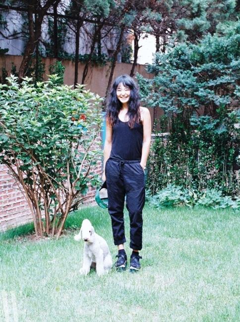 푸른 잔디와 나무들이 자리한 집 뒤편의 정원에 선 디자이너 김재현, 그리고 그녀의 사랑을 독차지하는 미모의 강아지 제타.