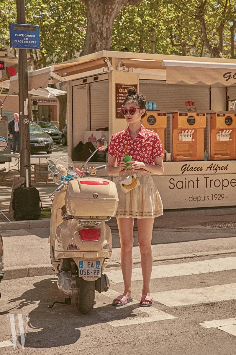 꽃무늬 블라우스는 The Kooples, 밴드 스커트는 Isabel Marant Etoile, 바나나 장식 가방은 Zara, 하트 프레임 선글라스는 Saint Laurent, 슬리퍼는 Nike 제품.