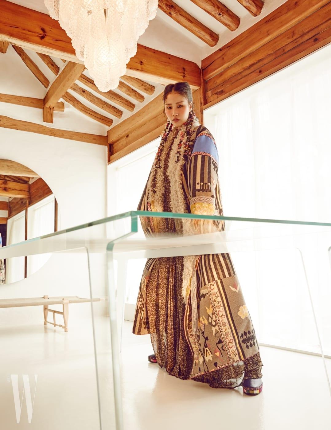 티베트, 몽골 등 유목민의 이국적인 정서가 담긴 롱 코트, 잔잔한 꽃무늬를 새긴 롱 드레스, 티베트 깃발이 연상되는 컬러 장식 부츠는 모두 Etro 제품.
