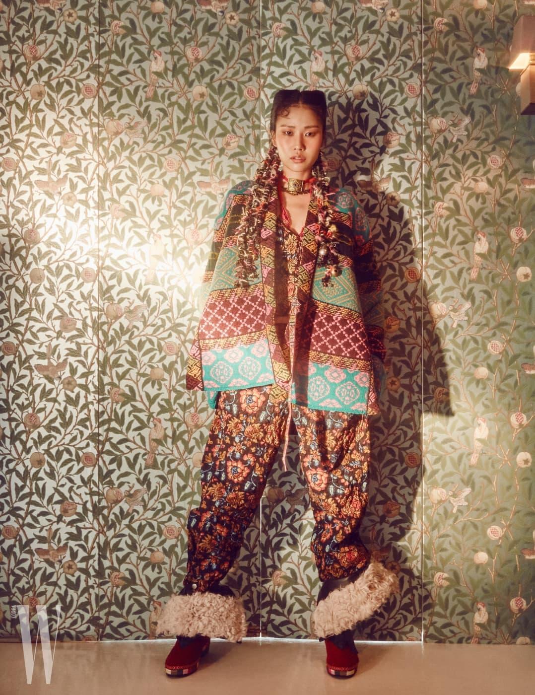 기모노 스타일의 니트 소재 아우터, 입체적인 꽃무늬 톱, 퀼트 팬츠, 양털 장식 에스닉 부츠, 분홍 색실과 금속 참 장식 목걸이, 함께 연출한 에스닉 금속 목걸이는 모두 Etro 제품.