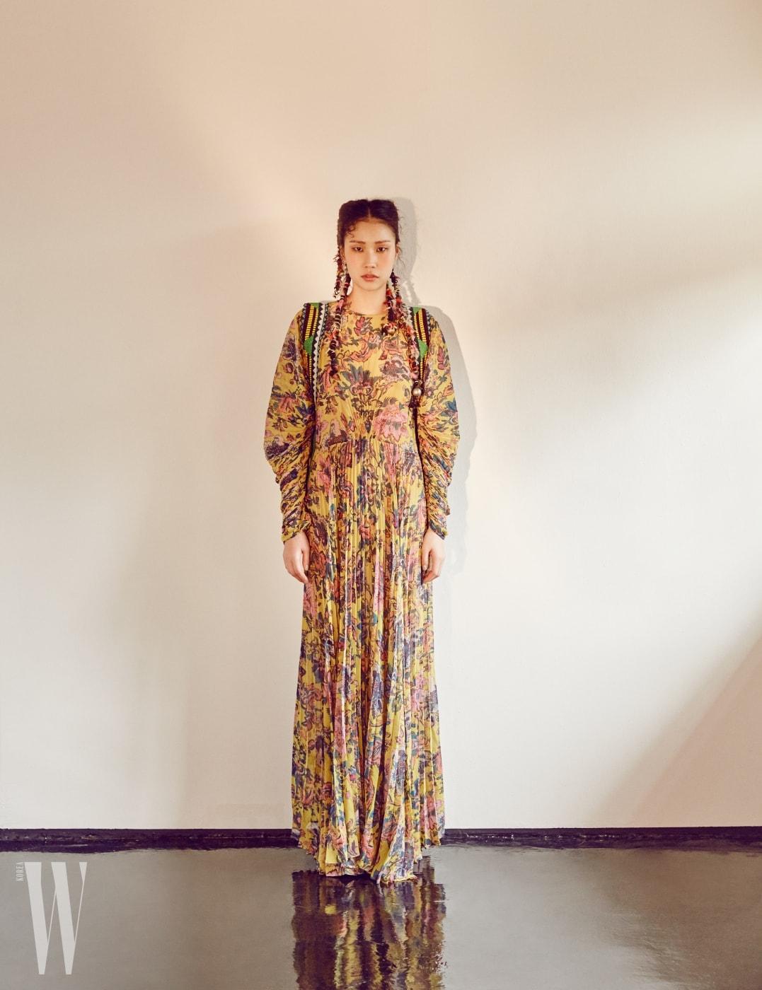 볼륨감 넘치는 주름 장식 페이즐리 롱 드레스, 민속적인 패턴이 돋보이는 배낭 끈 모티프의 액세서리는 Etro 제품.