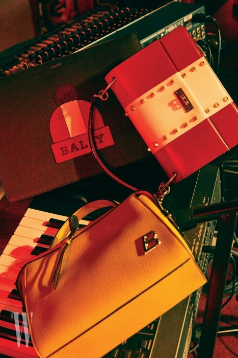 모자 모양이 그려진 클러치, 스터드 장식 핸드백, 노란색 가죽 토트백, 레오퍼드 송치 스커트, 자넬 (Janelle) 스터드 플랫 슈즈, 자넬 (Janelle) 카드 패턴 플랫 슈즈는 모두 BALLY 제품.
