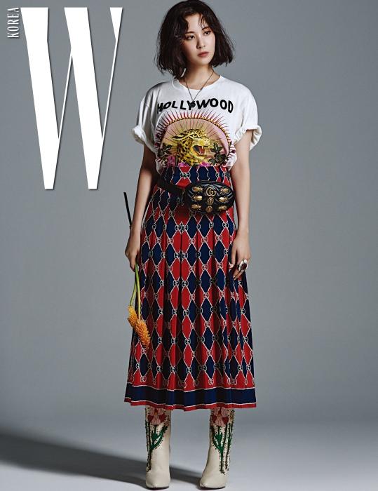 강렬한 프린트의 티셔츠와 주름 스커트, 곤충 모티프의 메탈 장식이 돋보이는 GG 마몽 백, 목걸이, 부츠, 반지는 모두 Gucci 제품.