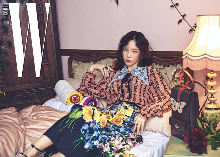 데님 칼라 장식, 그래픽 무늬 블라우스, 화사한 정원을 연상시키는 꽃무늬 스커트, 진주 장식 스트랩 샌들, 레진 소재의 나방 잠금 장식이 눈길을 끄는 숄더백, 반지, 귀고리는 모두 Gucci 제품.