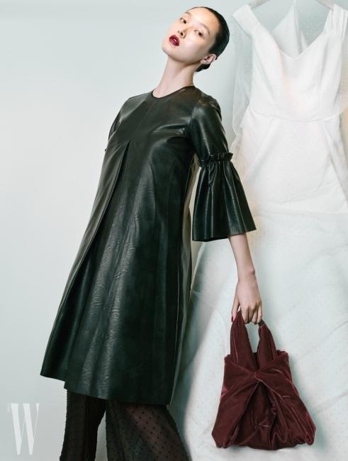 러플 장식의 부드러운 가죽 드레스, 안에 입은 도트 무늬 시스루 팬츠, 버튼을 잠가 형태를 만들 수 있는 벨벳 숄더백은 모두 MM6 제품.