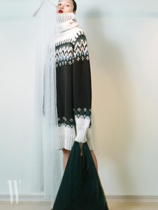 목이 높게 올라오는 터틀넥 니트 스웨터, 청록색 벨벳 숄더백은 MM6 제품.