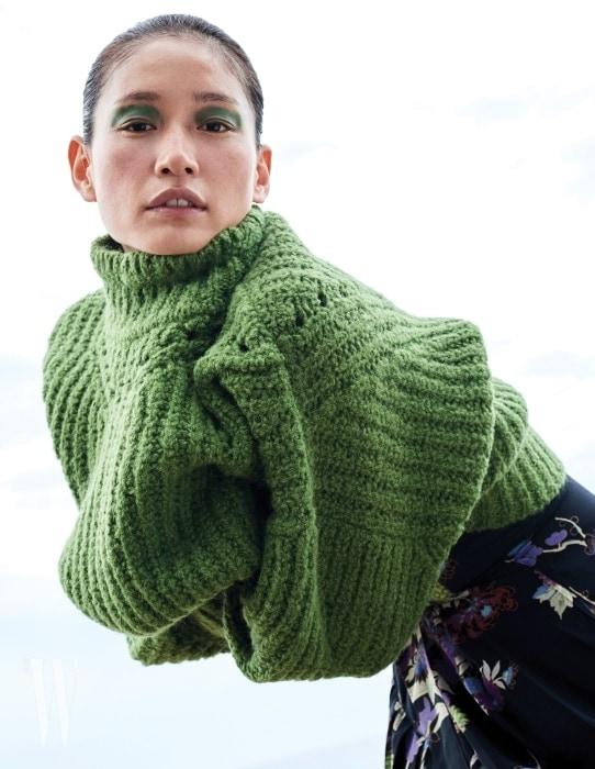 연두색 오버사이즈 터틀넥 니트 스웨터, 안에 입은 꽃무늬 비대칭 실크 드레스는 Isabel Marant 제품.