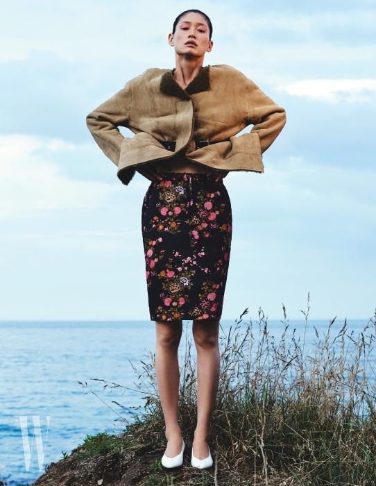 벨트가 달린 부드러운 무톤 코트, 실크 소재의 꽃무늬 스커트는 Isabel Marant, 하얀색 레트로 펌프스는 Isabel Marant Etoile 제품.