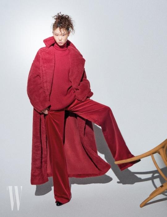 붉은색 터틀넥과 베스트, 벨벳 팬츠, 테디베어 코트, 검은색 부티는 모두 Max Mara 제품.