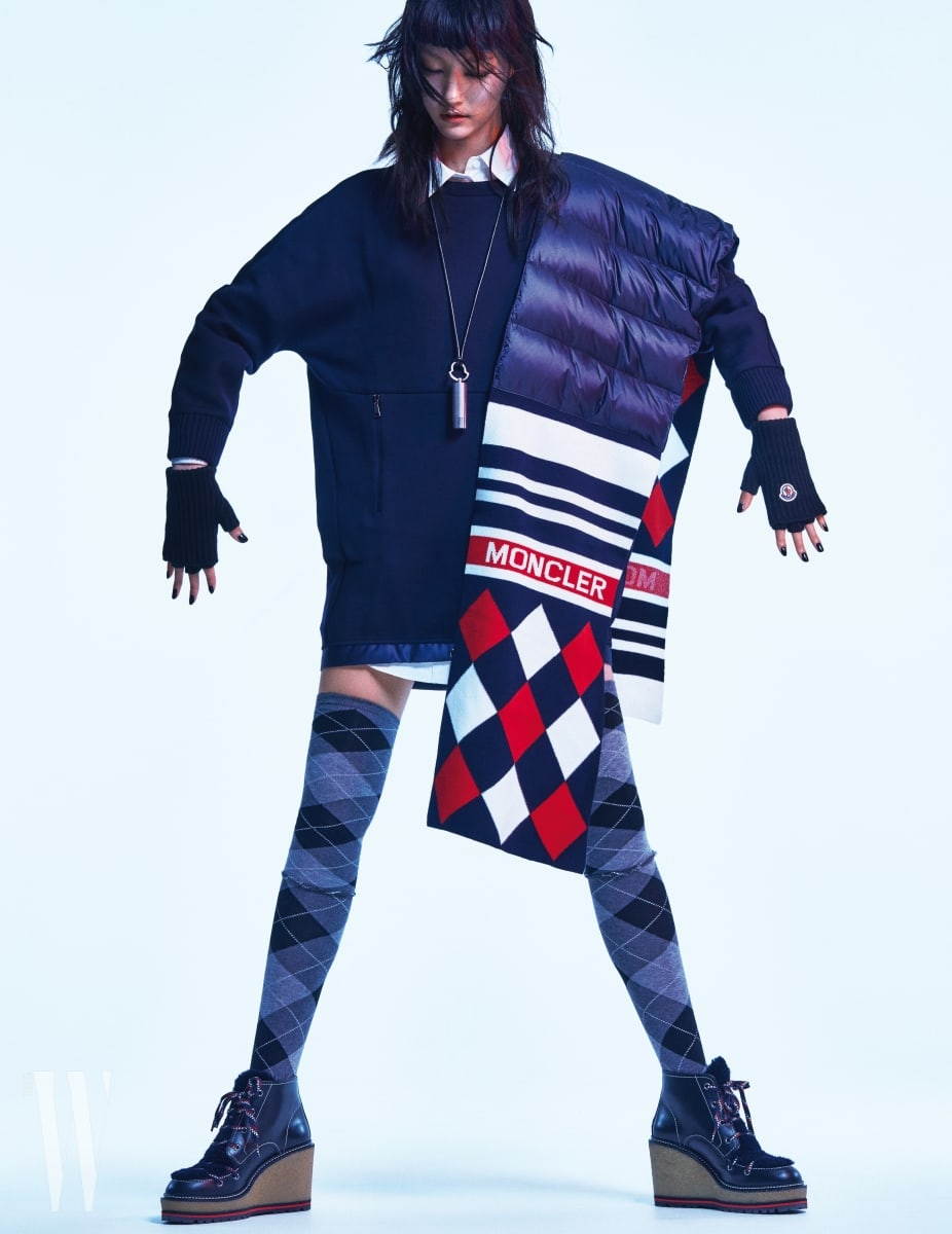 스웨트셔츠 스타일의 원피스, 안에 입은 흰색 롱 셔츠, 어깨에 두른 패딩과 니트 소재가 믹스된 아가일 패턴 머플러, 가죽 끈 네크리스, 핑거리스 장갑, 아웃도어 스타일의 플랫폼 힐 슈즈는 모두 Moncler 제품.