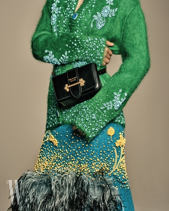 금속 버클이 장식된 사각 벨트 백은 프라다 제품. 가격 미정.비즈 자수가 놓인 초록색 앙고라 니트, 타조털이 달린 비즈 스커트는 프라다 제품. 가격 미정.