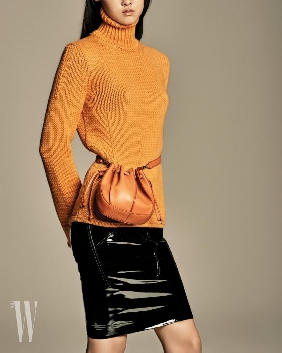 허리에 감아 연출할 수 있는 오렌지색 숄더백은 질샌더 제품. 1백70만원대. 오렌지색 터틀넥 니트 톱은 보테가 베네타 제품. 가격 미정. 페이턴트 소재의 검정 스커트는 톰 포드 제품. 가격 미정.
