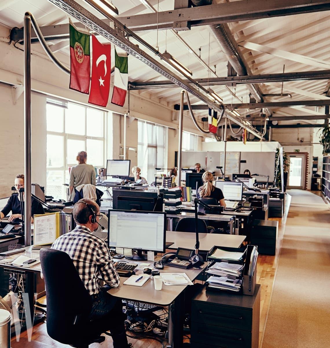 8 모든 안경테는 장인이 직접 디자인하고 수공 제작되며 전 세계 138개국에 공급된다. 천장에 걸린 국기는 해당 지역을 담당하고 있음을 뜻한다.
