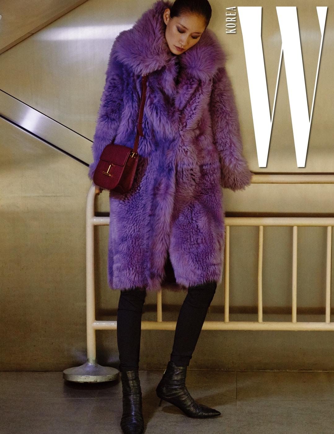 극적인 부피감의 시어링 양털 소재 코트, 슬림한 테일러드 팬츠, 버건디 색상의 '타라' 백, 날렵한 라인의 앵클부츠는 모두 Tom Ford 제품.