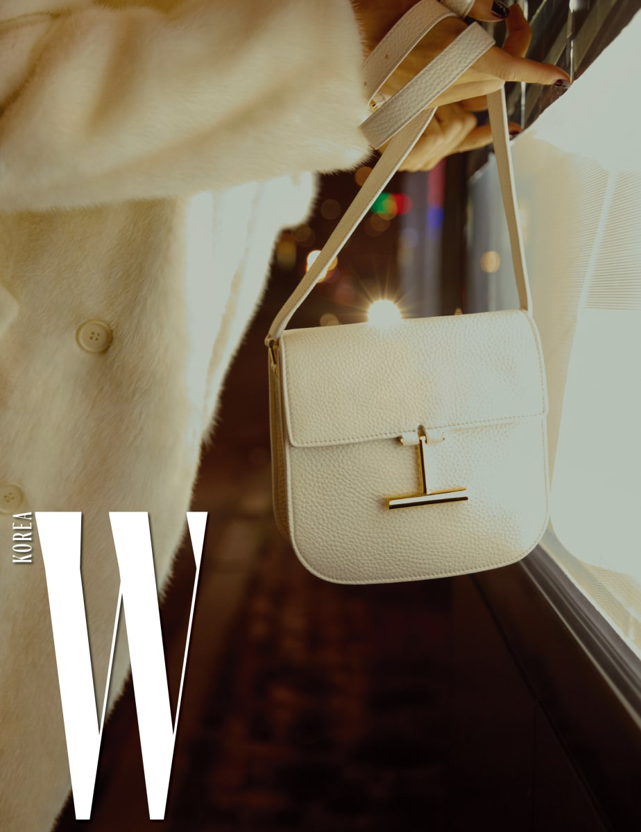 클래식한 디자인의 밍크 코트와 조각적인 버클이 시선을 끄는 '타라' 백은 Tom Ford 제품.