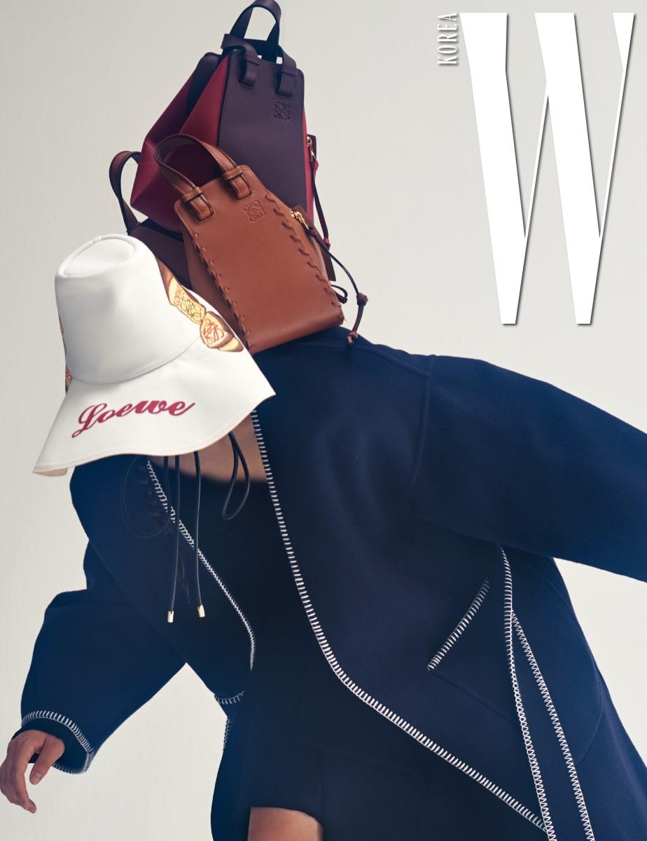 과감한 스티치가 돋보이는 부드러운 캐시미어 코트, 안에 입은 검은색 톱과 스커트, 팝아트적인 프린트의 토스트 모자, 가죽 스티치가 돋보이는 갈색 해먹 백, 갈색과 검붉은 빨강의 컬러 조합이 인상적인 해먹 백은 모두 Loewe 제품.