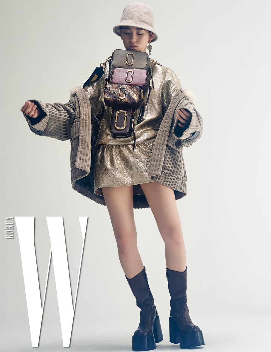 큼직한 회색 코듀로이 코트, 안에 입은 골드 미니 드레스, 베이지색 플로피 모자, 크리스털을 장식한 화려한 키 이어링, 차곡차곡 쌓아 올린 다채로운 색깔의 스냅샷 백, 두툼한 굽이 인상적인 부츠는 모두 Marc Jacobs 제품.