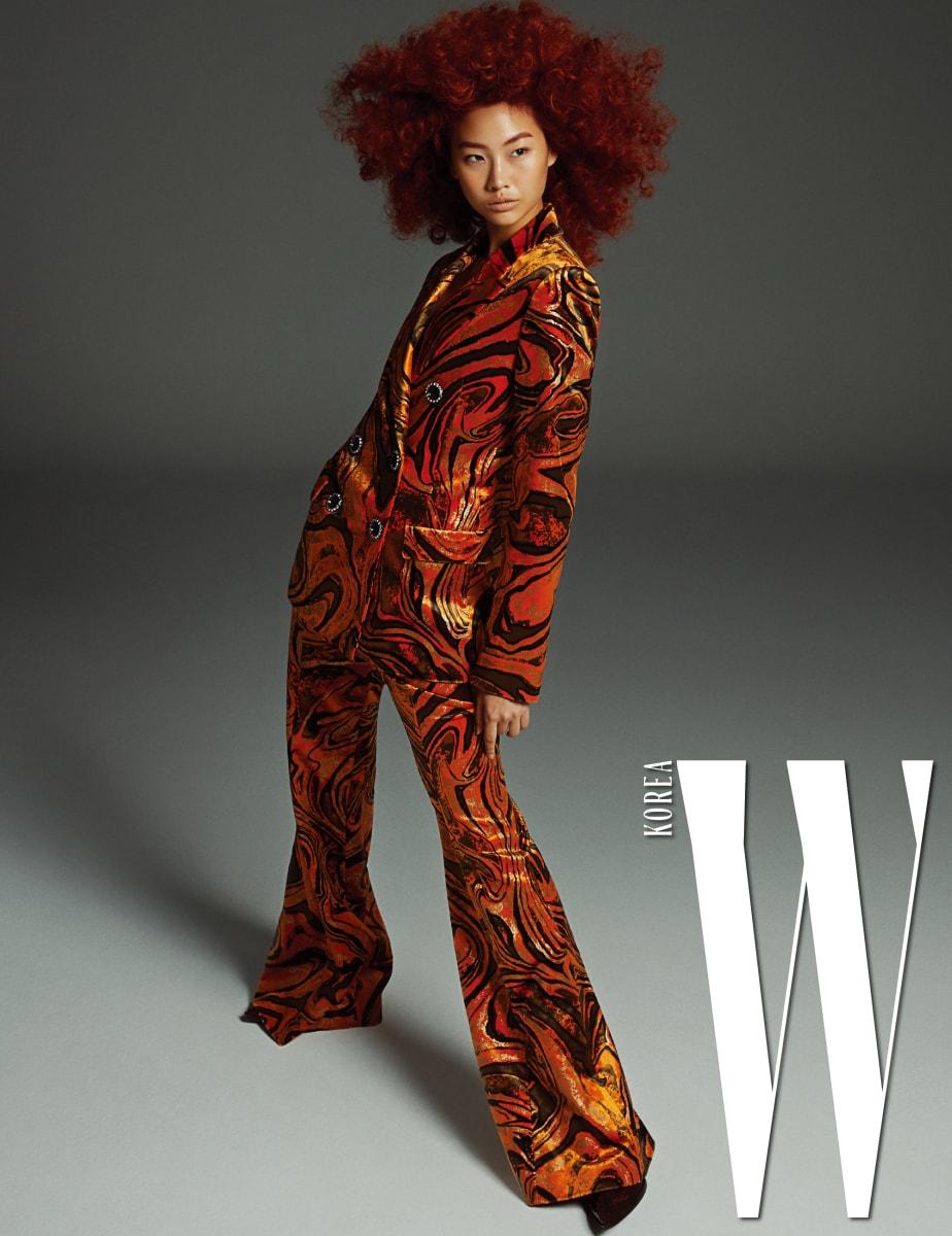 마블링 패턴의 더블브레스트 재킷과 밑으로 내려갈수록 핏이 넓어지는 팬츠, 슈즈는 모두 Emilio Pucci 제품.