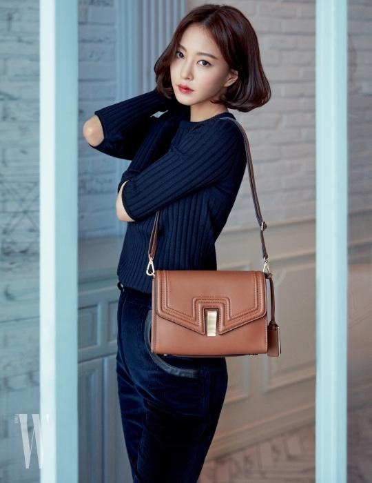 가을의 색감이 연상되는 클래식한 '나오미' 백은 Joy Gryson 제품. 소매 중간의 커팅이 인상적인 니트 스웨터, 코듀로이 소재 부츠컷 팬츠는 모두 Nina Ricci 제품.