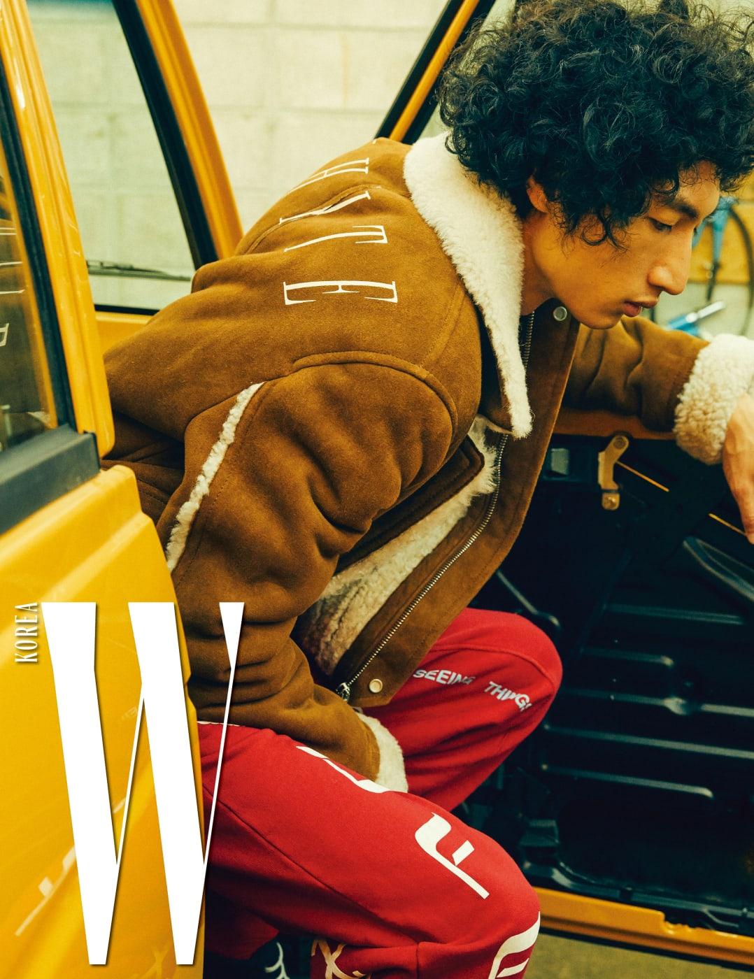 스웨이드 소재의 시어링 재킷과 프린트 티셔츠, 빨간색 스웨트 팬츠는 모두 Off -White 제품.