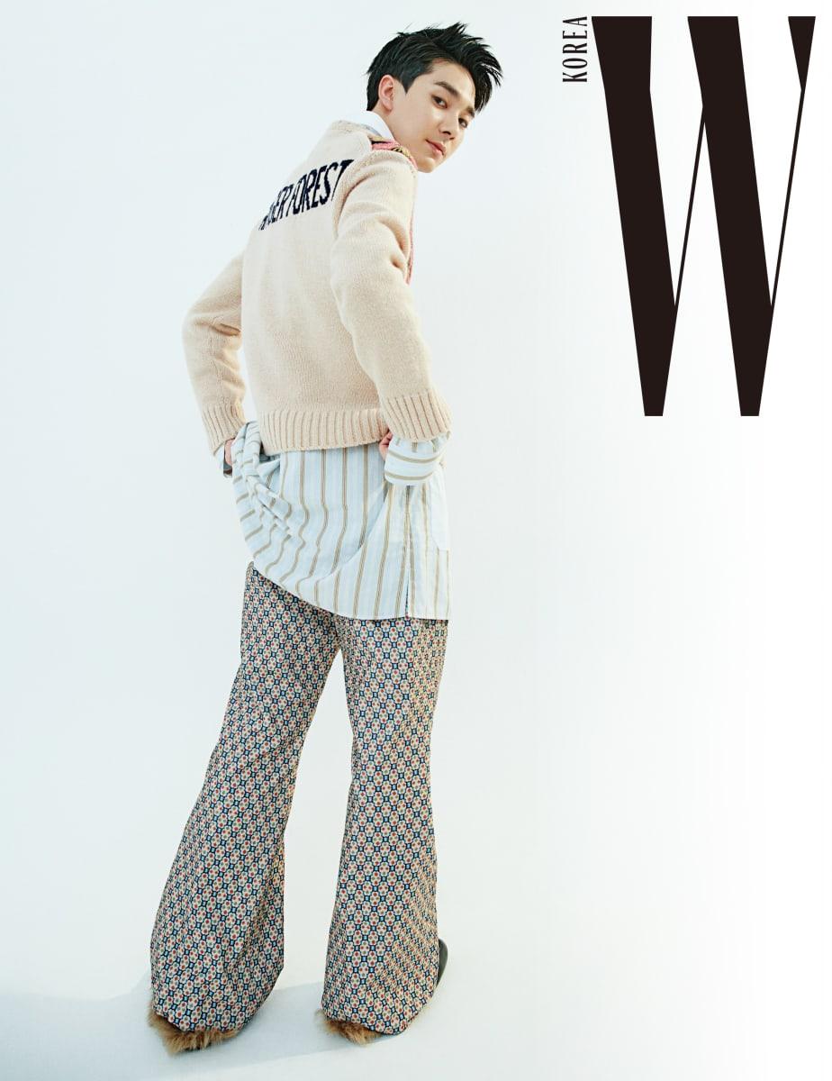 아론이 입은 분홍빛 패턴 니트와 안에 입은 줄무늬 롱 셔츠, 통이 넓은 패턴 팬츠, 퍼 블로퍼는 모두 구찌 제품.