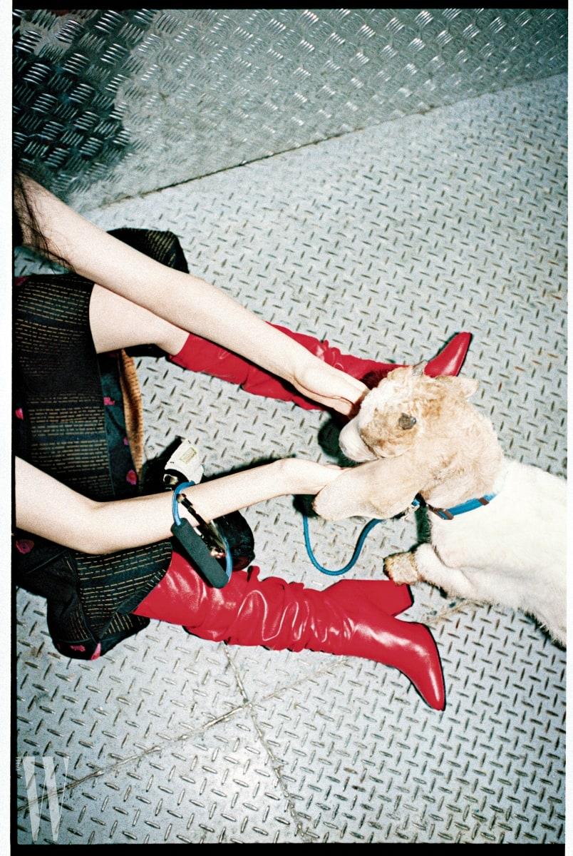 주름이 잡힌 붉은색 부츠는 스튜어트 와이츠먼 제품. 가격 미정. 오른손에 낀 복주머니 형태의 가방은 발렌티노 제품. 가격 미정. 스커트는 프로엔자 스쿨러 제품. 가격 미정.