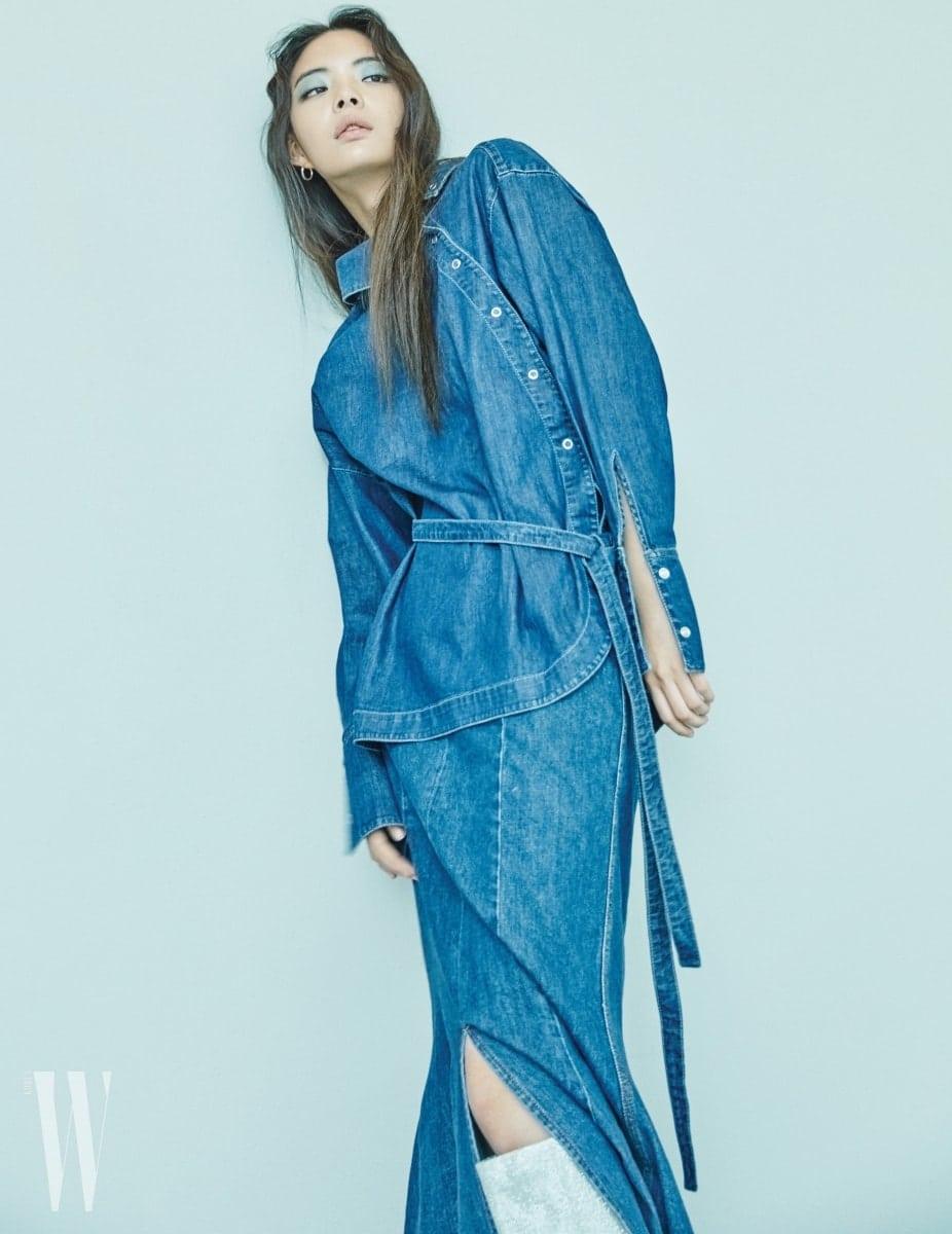 비대칭 단추 장식의 데님 셔츠, 트임 장식 롱스커트는 스텔라 매카트니 제품. 가격 미정. 반짝이는 은색 부츠는스튜어트 와이츠먼 제품. 가격 미정.